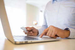 使用信用卡和膝上型计算机的人,购物在line.indoor 图库摄影