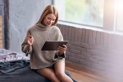 使用信用卡和膝上型计算机的俏丽的妇女在床 免版税库存图片