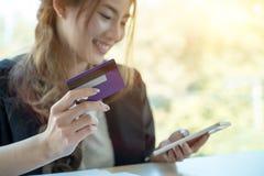 使用信用卡的亚裔妇女在网上购物与智能手机在 库存照片