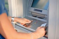 使用信用卡的人特写镜头对撤出从Atm机器的金钱 免版税库存图片