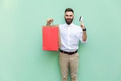 使用信用卡的商人网上购物的 看照相机和暴牙的微笑 免版税图库摄影