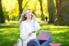 使用信用卡的妇女在网上购物与膝上型计算机在同水准 免版税图库摄影