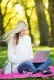 使用信用卡的妇女在网上购物与膝上型计算机在同水准 免版税库存照片
