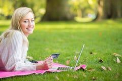 使用信用卡的妇女在网上购物与膝上型计算机在同水准 图库摄影