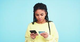 使用信用卡的非洲俏丽的夫人和做与她的智能手机的网上命令在蓝色背景墙壁 影视素材