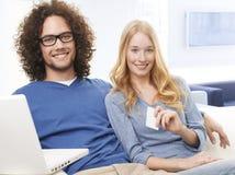 使用信用卡的年轻微笑的夫妇和购物在互联网上 免版税库存照片