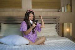 使用信用卡网上银行的年轻美丽和愉快的亚洲韩国女人在家卧室与手机在床微笑的o上 库存照片