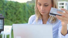 使用信用卡,咖啡馆使用膝上型计算机和在网上购物的少妇 股票视频