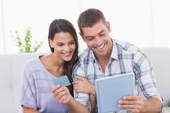 使用信用卡,结合购物在网上在数字式片剂 库存图片