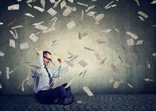 使用修造网上营业收益金钱的膝上型计算机的商人根据美金兑现跌倒的雨 免版税图库摄影