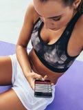 使用健身房应用程序的女运动员为锻炼 免版税库存图片