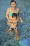 使用充满在水池的幸福的母亲和儿子 免版税库存照片