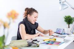 使用写生簿的年轻女性艺术家图画剪影与在她的工作场所的铅笔在演播室 侧视图画象  库存照片