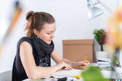 使用写生簿的年轻女性艺术家图画剪影与在她的工作场所的铅笔在演播室 侧视图画象  库存图片
