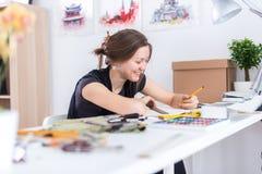 使用写生簿的年轻女性艺术家图画剪影与在她的工作场所的铅笔在演播室 侧视图画象  免版税库存照片