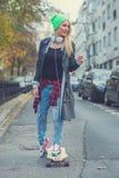 使用冰鞋板的逗人喜爱的年轻都市妇女 免版税图库摄影