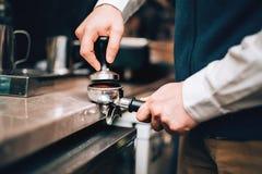 使用准备与拿铁泡沫的咖啡机器的Barista新鲜的咖啡在咖啡店和餐馆 免版税库存照片