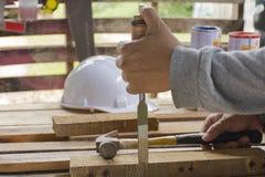 使用凿子和锤子的木匠在他的有板条的手 关闭 库存照片