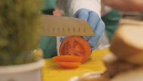 使用刀子的厨师的手为切在圈子切片和片断的蕃茄在餐馆 库存照片