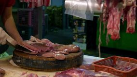 使用刀子的摊位供营商为切在木板的片断未加工的肾脏猪肉 影视素材