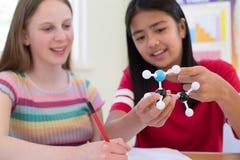 使用分子式样成套工具的两个母学生在科学教训 库存图片