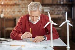 使用分度器的灰发的人,当描绘图纸时 免版税库存照片