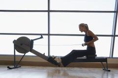 使用划船器的妇女在健身俱乐部 图库摄影