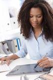 使用制图桌的年轻设计师 免版税图库摄影