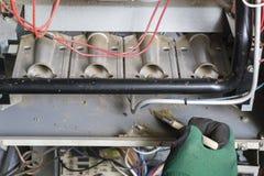 使用刷子的技术员清洗在燃烧器下 图库摄影