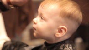 使用剪刀,在美发师` s商店,一个小孩子是被剪的头发 影视素材