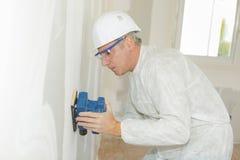 使用力量沙磨机的成熟建造者在墙壁上 免版税库存图片