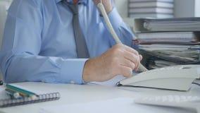 使用办公室输送路线电话的商人图象在认为的档案里 库存照片