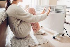 使用加热器在家在冬天 温暖她的手的妇女 取暖季节 库存照片