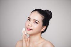 使用化装棉的愉快的微笑的美丽的亚裔妇女清洗sk 库存照片
