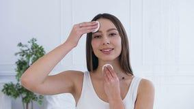 使用化装棉的美丽的深色的妇女画象  股票录像