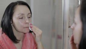 使用化装棉的美丽的深色的妇女 去除妇女的构成 影视素材