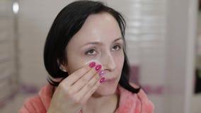 使用化装棉的美丽的深色的妇女 去除妇女的构成 股票录像