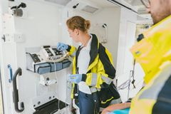 使用医疗技术的医务人员在救护车汽车 免版税库存图片