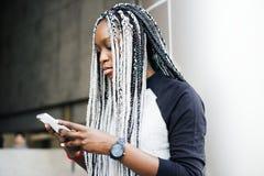 使用单独智能手机的非洲妇女 免版税图库摄影
