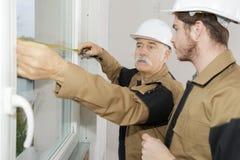 使用卷尺窗口的工作者在建造场所 免版税库存图片