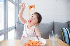 使用叉子的俏丽的女孩吃意粉由她自己 图库摄影