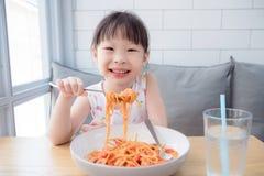 使用叉子的俏丽的女孩吃意粉由她自己 免版税库存图片