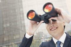 使用双筒望远镜的微笑的商人,反射 库存照片