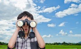 使用双筒望远镜的男孩在领域 免版税库存图片