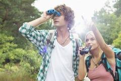 使用双筒望远镜的男性远足者,当显示他某事的妇女在森林时 库存照片
