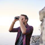 使用双筒望远镜的年轻人户外为鸟的监视人 免版税库存图片