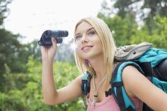 使用双筒望远镜的年轻女性远足者在森林 免版税库存图片