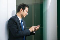 使用发短信在办公室外面的手机app的商人在有摩天大楼大厦的都市城市在背景中 免版税库存图片