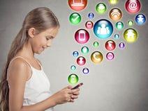使用发短信在智能手机的少年女孩 免版税图库摄影