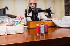 使用古板的缝纫机的老人 库存图片